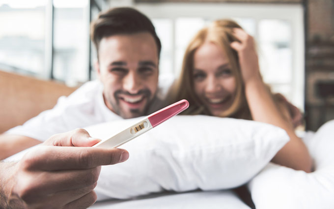 Happy couple holding a positive pregnancy test