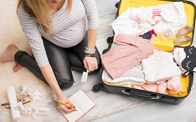 Pregnant woman packing her bag for hospital marking things off in a notebook