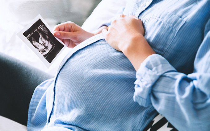 Pregnant woman holding an ultrasound whilst cradling her belly